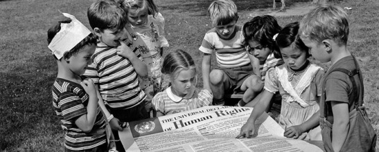 "In 1950, on the second anniversary of the adoption of the Universal Declaration of Human Rights, students at the UN International Nursery School in New York viewed a poster of the historic document.   After adopting it on December 10, 1948, the UN General Assembly had called upon all Member States to publicize the text of the Declaration and ""to cause it to be disseminated, displayed, read and expounded principally in schools and other educational institutions, without distinction based on the political status of countries or territories.""  (UN Photo)"